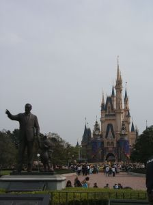 A statue of Walt Disney and Mickey with Cinderella's Castle in the background.