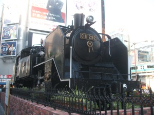 The engine of Japan's first train in front of 新橋駅 (Shinbashi Stn (one of Japan's oldest train stations))