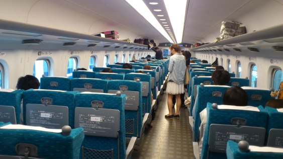Inside the 新幹線 (bullet train).  (That person isn't known to us).